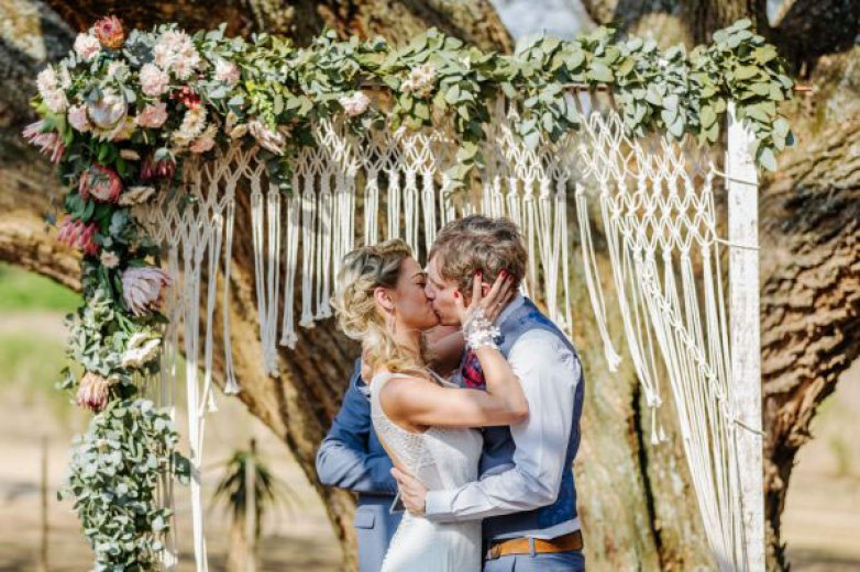 Bride and Groom kissing in front of a macrame wedding arch