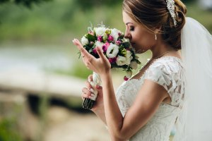 Bride smelling wedding flowers