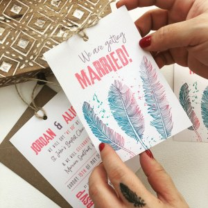 hands holding wedding invitation boho feathers