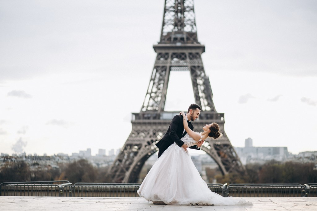 bride and groom posing in front of the Eiffel Tower