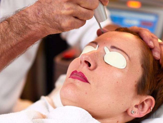Womans face under laser skin treatment