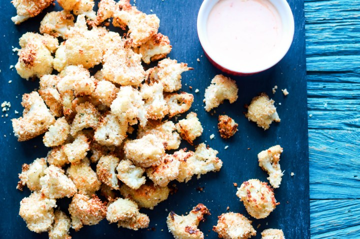 panko and asiago crusted popcorn cauliflower-featured-on a board-sauce on the side