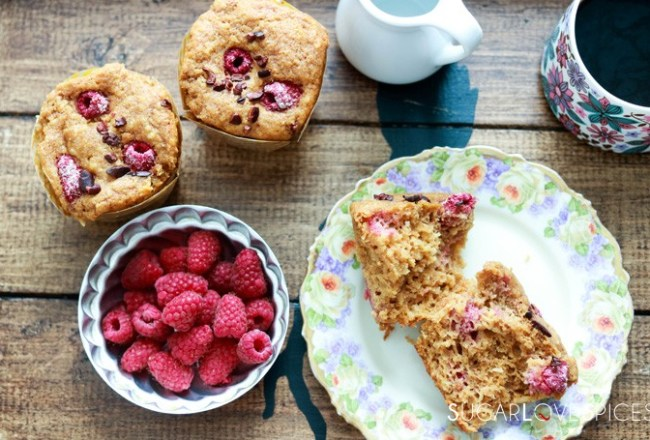 coconut raspberry spelt muffins-on a tray, with raspberries, one muffin open
