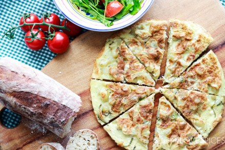 Frittata patate e cipolle-frittata sliced on a board with bread and salad on the side