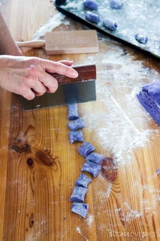 Homemade purple potato gnocchi- cutting gnocchi with scraper on wood board