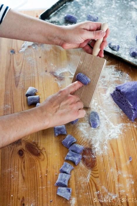 Homemade purple potato gnocchi-rolling gnocchi on wood gnocchi board