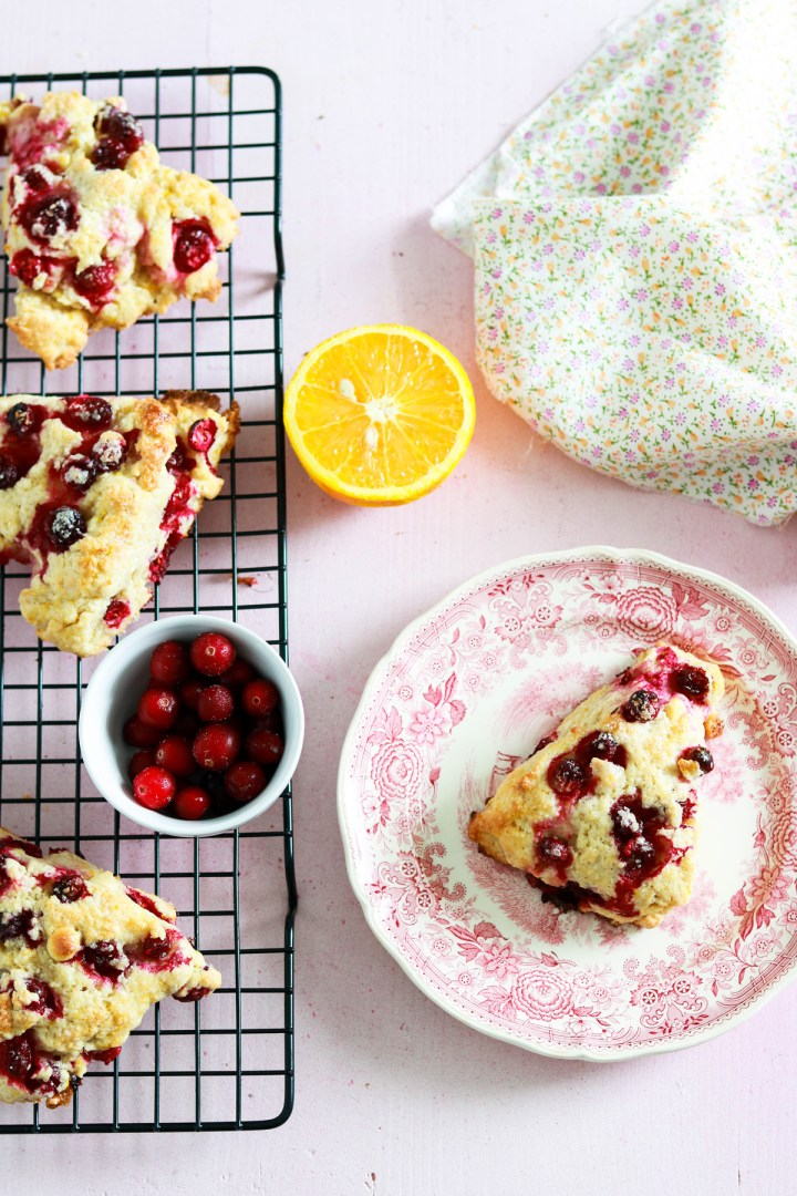 one scone on a plate the rest on a rack with cranberries