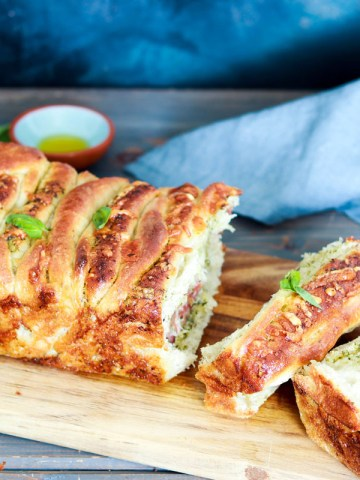 Pesto and Salami Pull-Apart Bread-feature-bread on woodboard-pulled apart