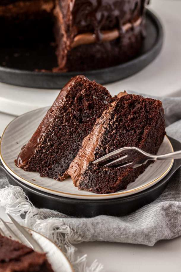 A closeup of a slice of chocolate cake with a fork digging into it