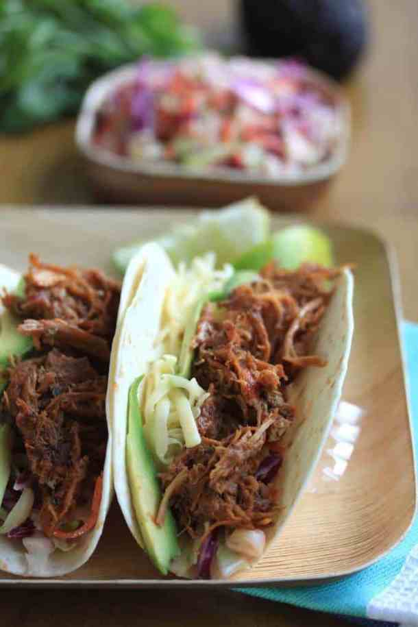 Pulled Pork Tacos by Sugar Salt Magic. LIghtly spiced and slow cooked to perfection, this pulled pork is then coated in a delicious barbecue sauce.