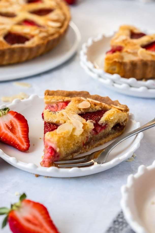 A slice of strawberry tart on a white plate with a fork sitting next to it. More slices in the background