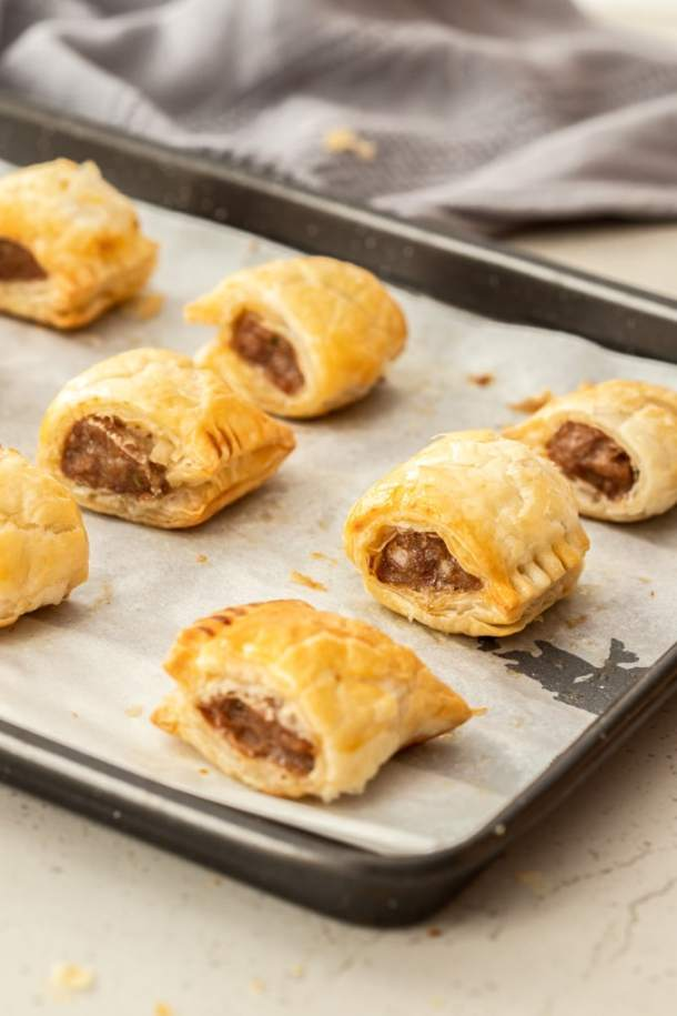 Freshly baked sausage rolls on a baking tray
