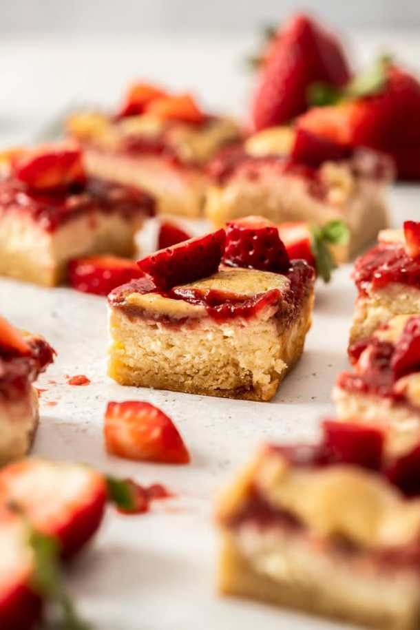 5 blondies on a plate surrounded by crumbs. Berries in the background