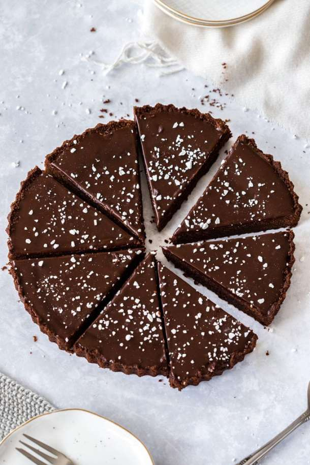 Birdseye view of a chocolate tart cut into 8 slices sitting on a concrete bench top