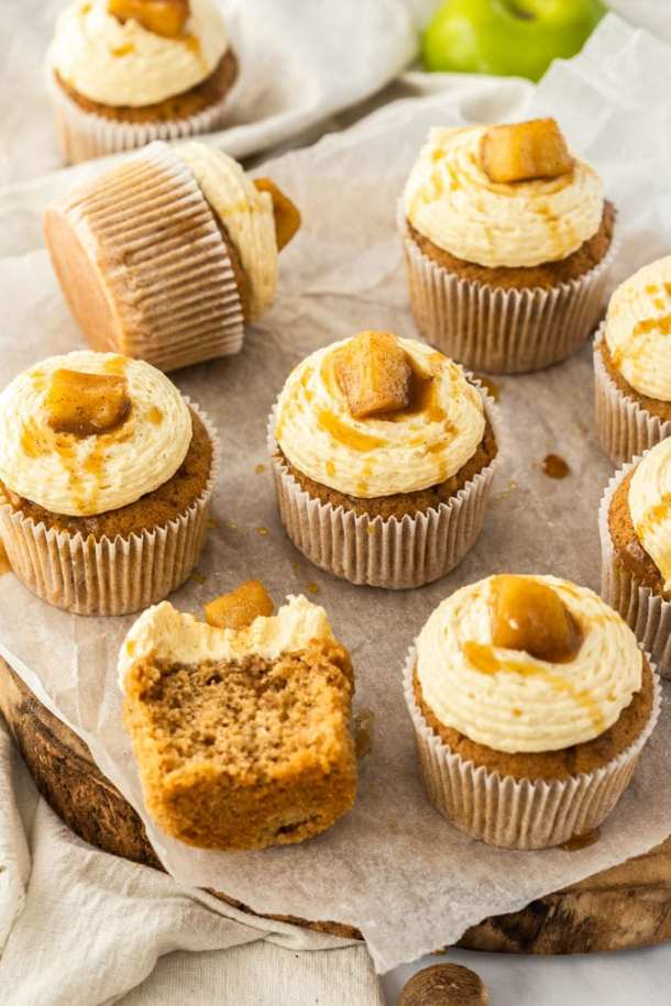 Apple pie cupcakes sitting on a wooden cake board on a marble background