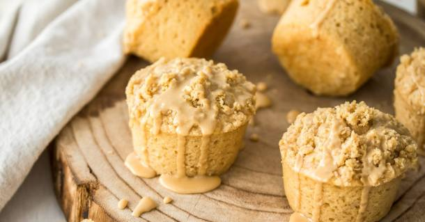 Coffee cake muffins on a board with the glaze running down the side