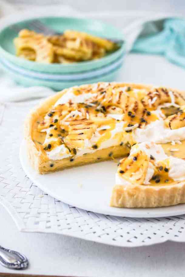 This Passionfruit Tart is a simple passionfruit curd custard filling in a crisp tart shell. It's all topped with grilled pineapple slices and coconut. Tropical dessert heaven.