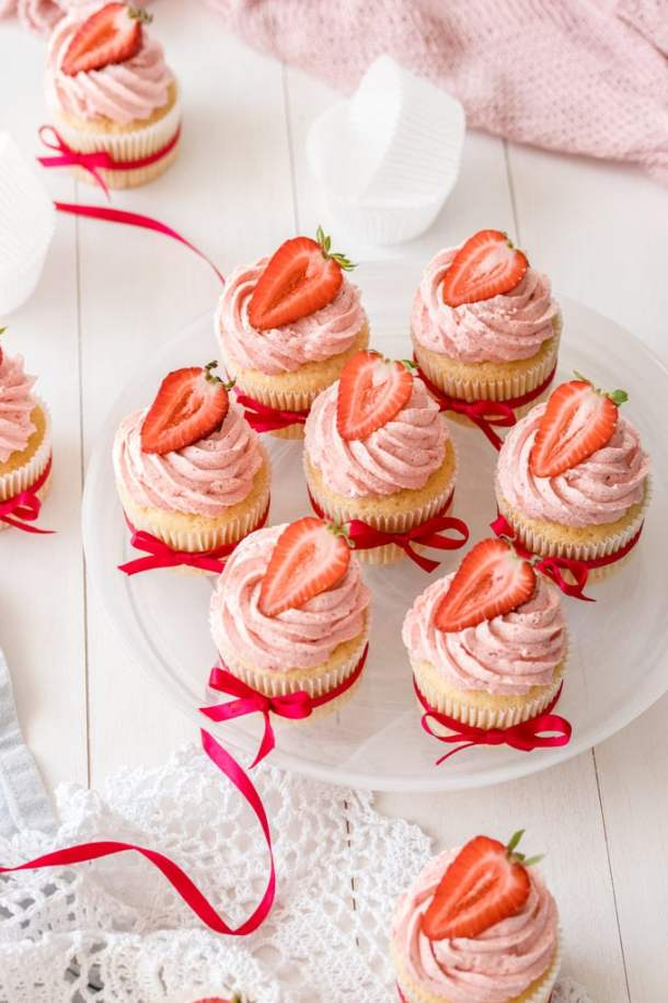 Top down view of a plate of 7 vanilla cupcakes with strawberry buttercream