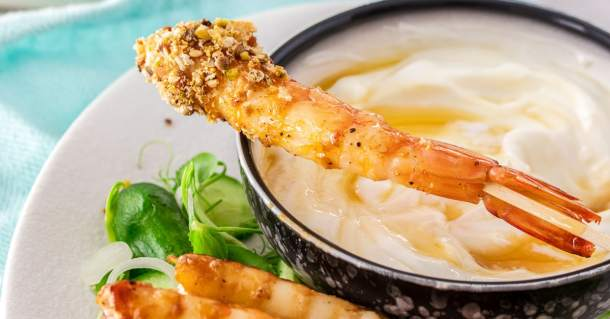 A dukkah crust prawn sitting on top of a bowl of yoghurt.