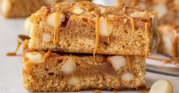 Two stack caramel blondies with caramel drizzling down the sides.