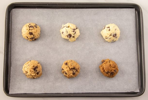 Six mounds of cookie dough on a baking tray