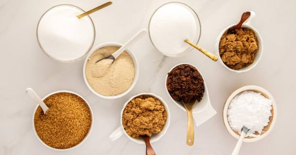 Eight types of sugar in bowls on a white background
