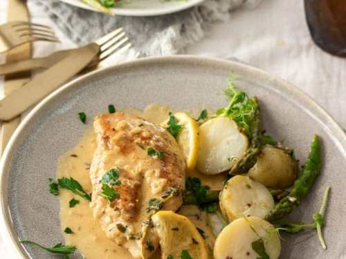 A grey plate with a chicken breast, potatoes and a cream sauce