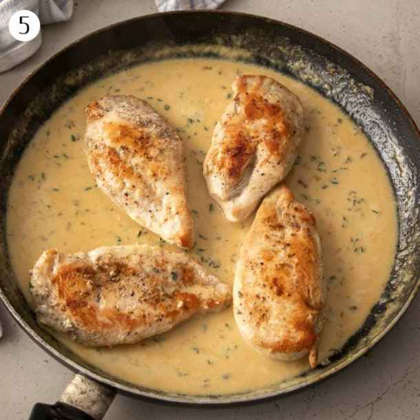 4 chicken breasts in a pan with creamy sauce.