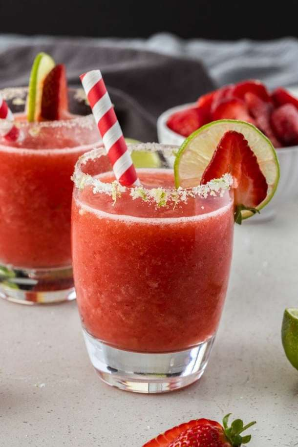 A frozen strawberry daiquiri in a glass with a red straw