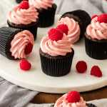 Closeup of a chocolate cupcake with raspberry frosting and topped with a fresh raspberry