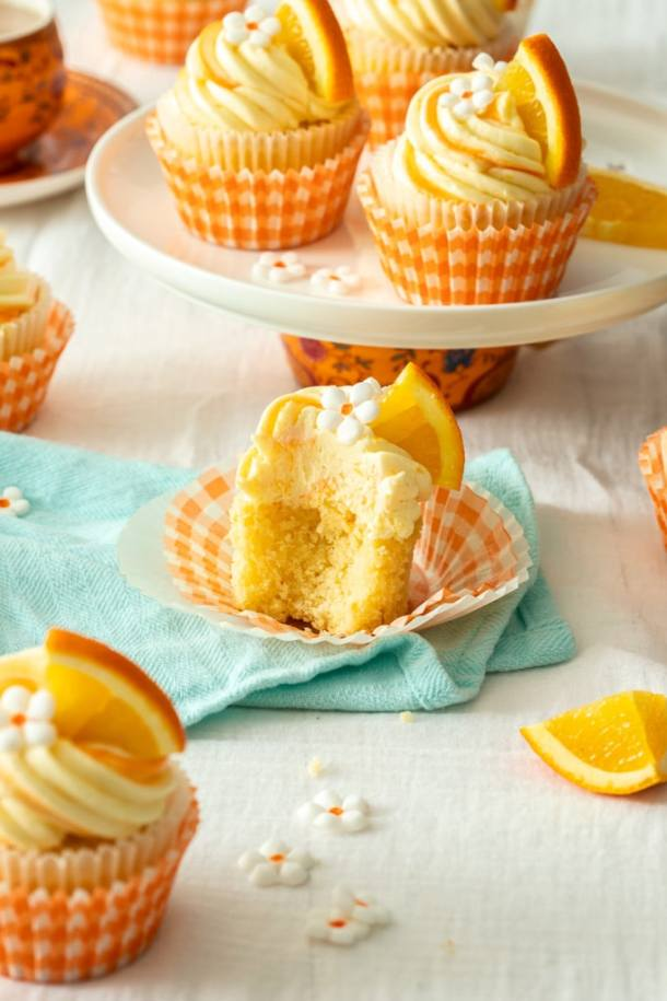 An orange cupcake cut open to reveal the fluffy texture sitting on an aqua teatowel