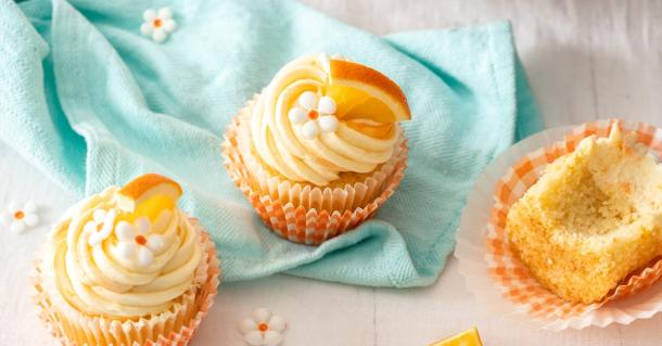 Three orange cupcakes with white buttercream sitting on an aqua tea towel
