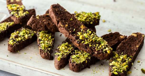 A stack of pistachio chocolate biscotti on a board