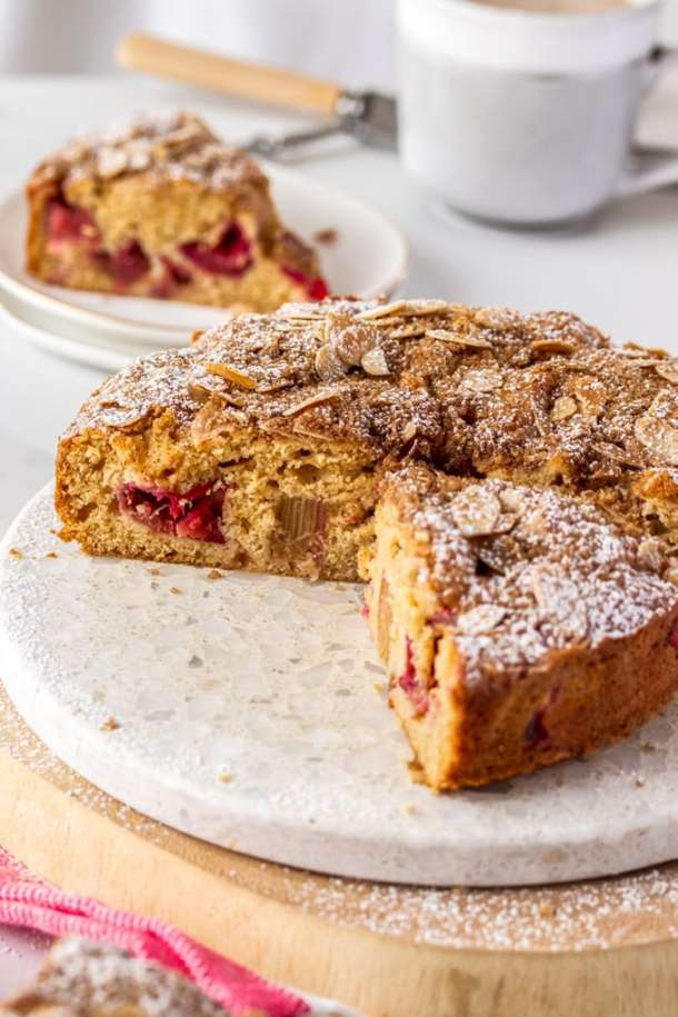 A rhubarb cake with a few slices cut out, sitting on a marble cake platter