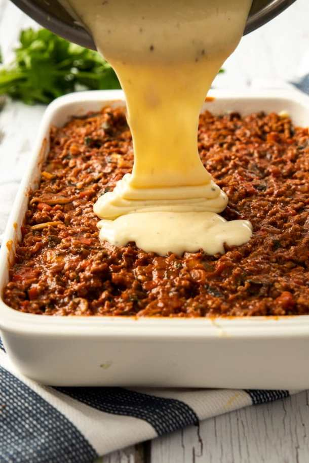 Bechamel sauce being poured on top of meat sauce in a white casserole dish