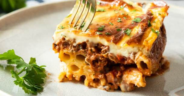 A slice of pastitsio on a grey plate with a fork digging into it