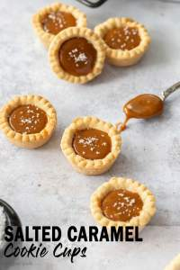 6 caramel cookie cups on a concrete background with a spoon filled with caramel next to them.