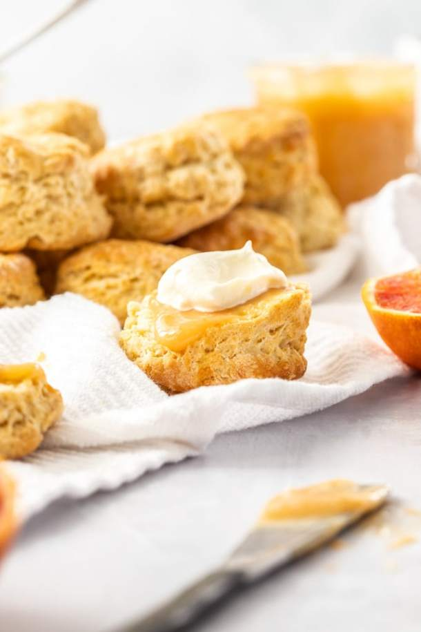 Half a scone topped with orange curd and cream sitting on a white tea towel. A pile of scones sits behind it