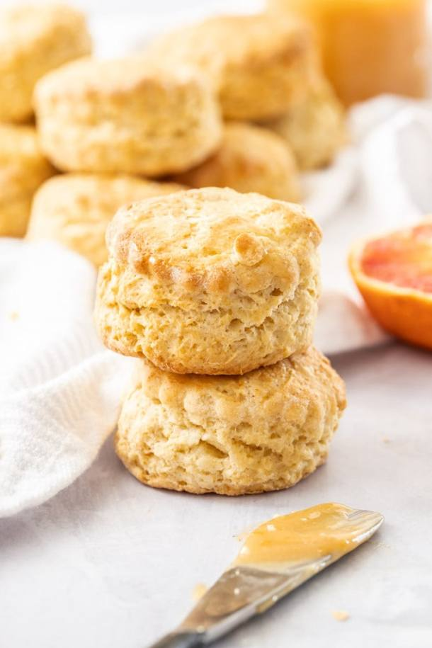 Two scones, one stacked on top of the other with a pile of scones in the background