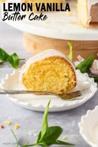 A slice of vanilla bundt cake on a white plate with a fork in front. Some lemon tree leaves scattered around
