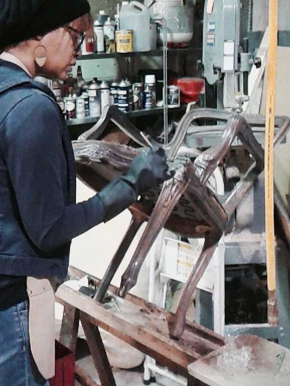 Upholstery Designer adding hand-painted patina details to chair