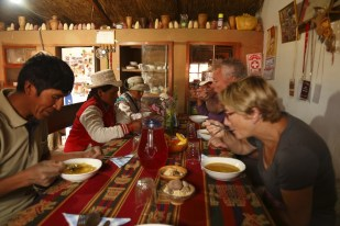 Travelers sit with local hosts over a delicious meal.