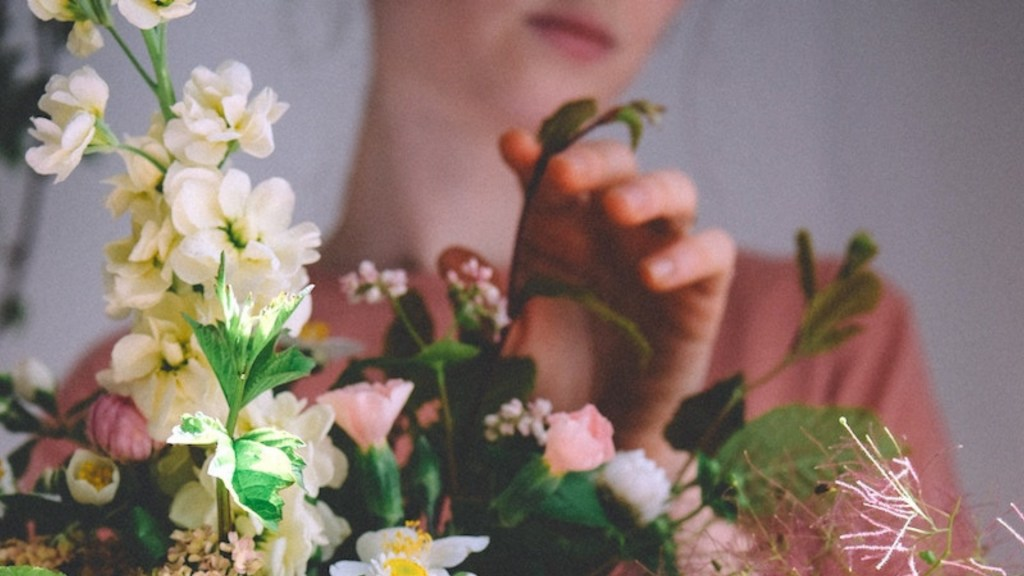 Close up of woman touching leaf in pink and white floral bouquet.