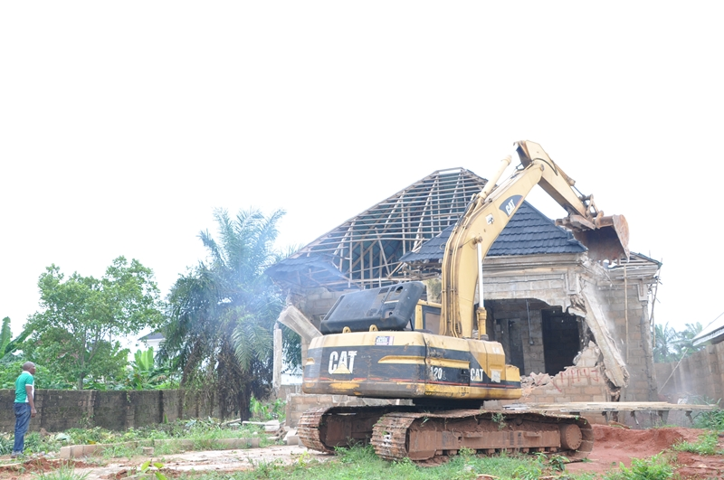 One of the illegal buildings constructed on a moat being demolished
