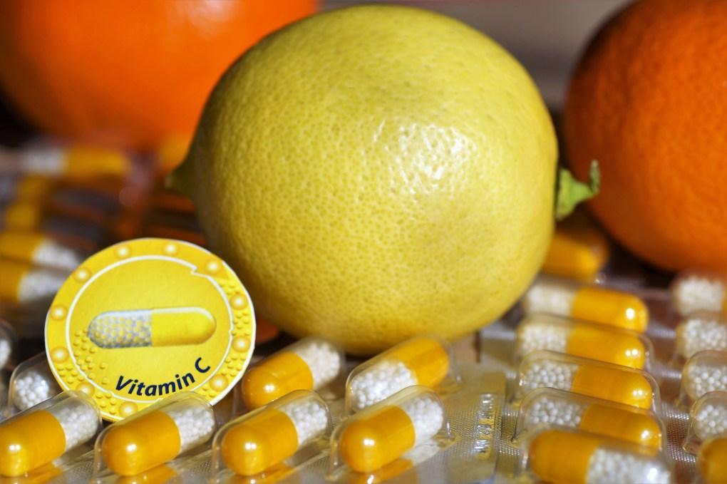 Imagem mostra frutas cítricas junto a comprimidos de vitamina C.