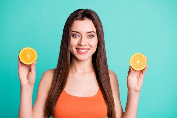 Imagem de uma mulher segurando laranjas.