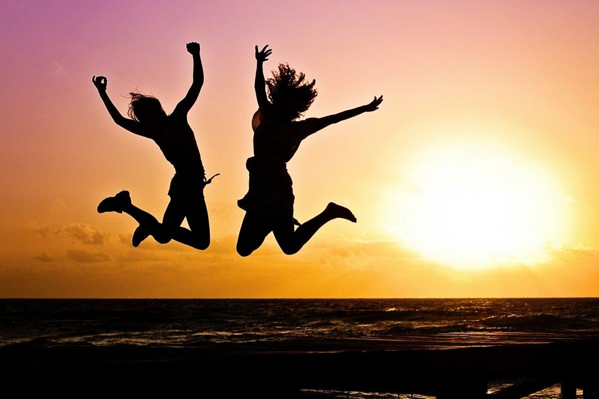 Duas pessoas pulando com por do sol no fundo.