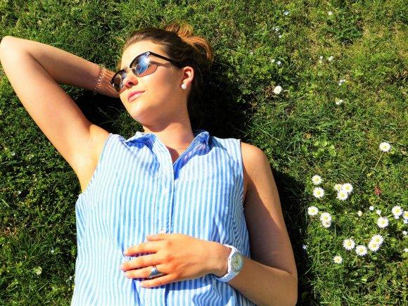 Mulher deitada na grama tomando sol.