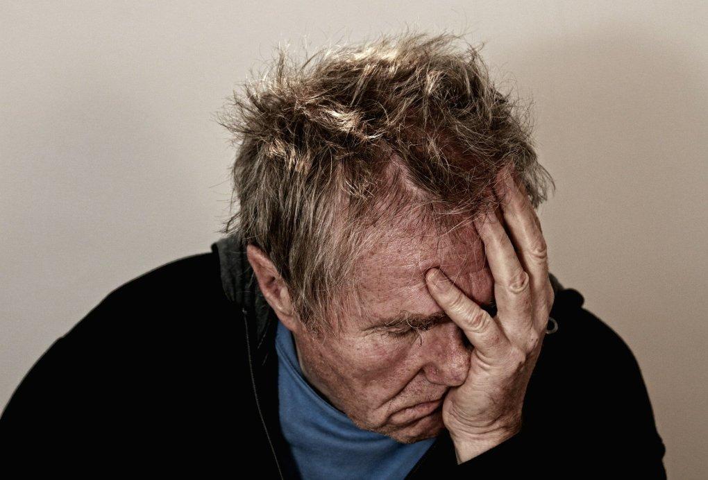 Imagem mostra um homem aparentemente sentindo dor.