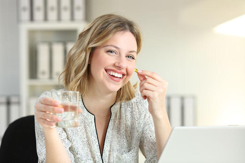 Imagem de uma mulher tomando um suplemento em cápsula.